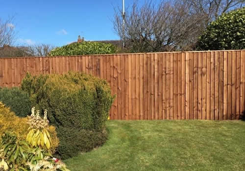 vertical board wooden fence installed on sunny day in westhoughton